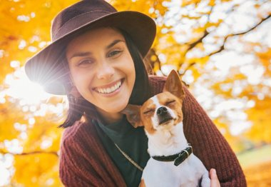 happy young woman with dog outdoors in autumn