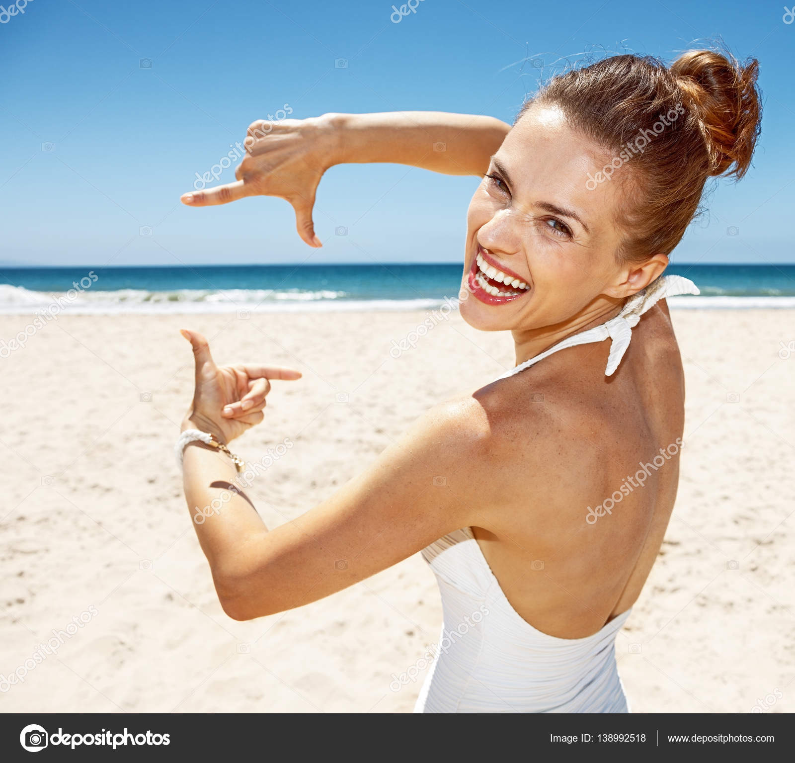 Sonriente mujer en traje de baño en el encuadre de la playa de arena ...