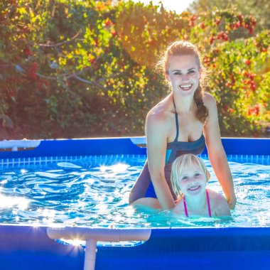 smiling active mother teaching child to swim in swimming pool