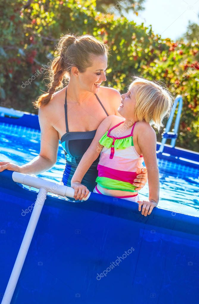 happy mother and child in swimming pool looking at each other