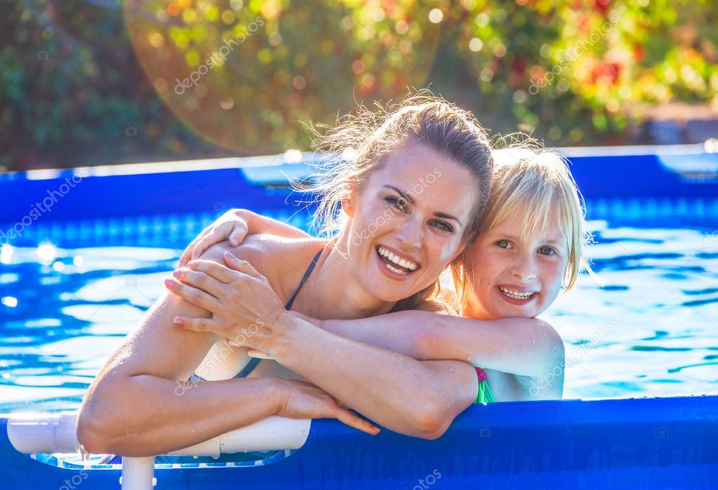 smiling active mother and child in swimming pool embracing