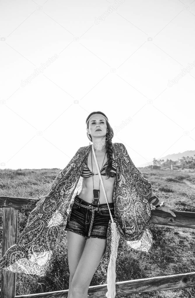 Bohemian vibe vacation. Portrait of young bohemian girl in jeans shorts and cape outdoors in the summer evening looking into the distance