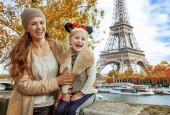 Fotografie Perfektní podzimní prázdniny v Disneylandu a Paříže. Ať se usmívám turisté matka a dcera v Minnie myší uši na nábřeží poblíž Eiffelova věž v Paříži sedět na parapetu