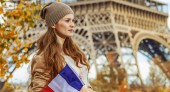 happy young elegant woman on embankment near Eiffel tower in Paris, France with flag