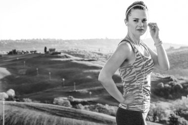 Fitness and magical views of Tuscany. Portrait of young fitness woman in sportswear in the front of scenery of Tuscany with headphones listening to the music