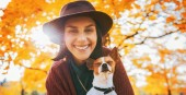 Fotografie Portrait of happy young woman with dog outdoors in autumn