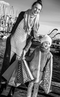 Full length portrait of happy trendy mother and child with shopping bags in Barcelona, Spain having fun time