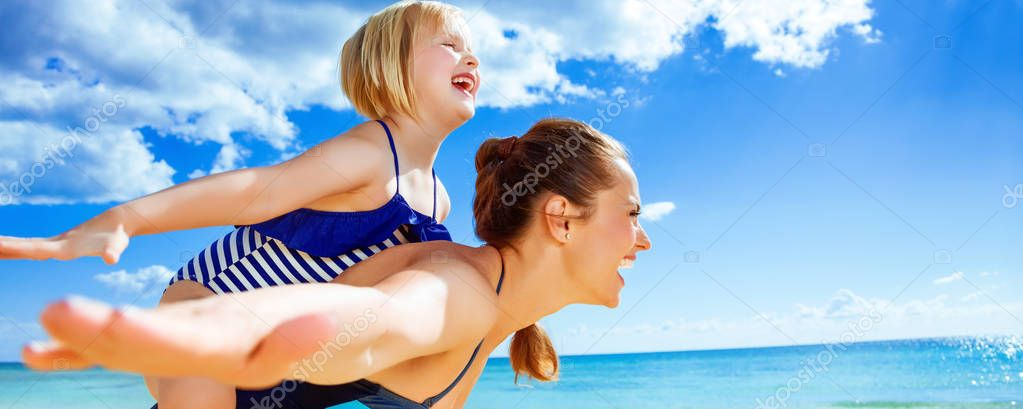 Sun kissed beauty. cheerful healthy mother and daughter in swimwear on the seacoast having fun time