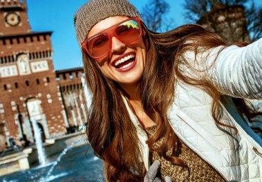 happy young woman near Sforza Castle in Milan, Italy taking selfie