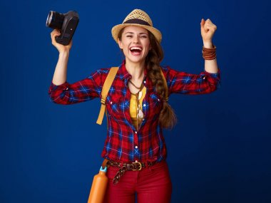 smiling healthy woman hiker with backpack and digital camera rejoicing on blue background