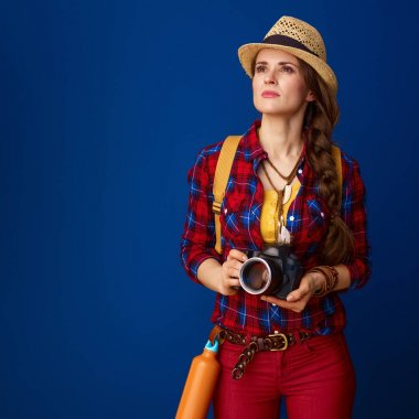 young proud woman hiker with backpack and  digital camera against blue background