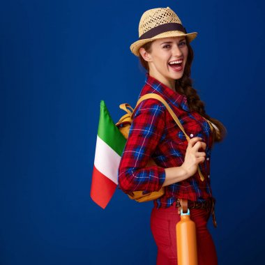 smiling healthy woman hiker with backpack and the flag of Italy