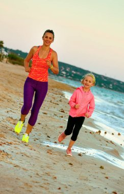 smiling fit mother and child in sport style clothes on the seacoast in the evening running