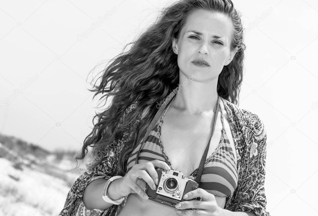 hippie young woman in swimsuit on the seacoast with vintage photo camera
