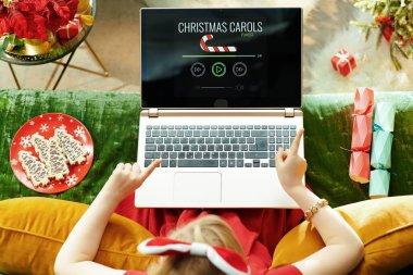 modern little princess listening Christmas songs on laptop