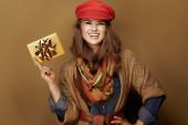 šťastný trendy 40 rok stará žena ukazující zlatý dárkový poukaz