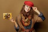 40 let stará žena se zlatou dárkovou kartou na bronzovém pozadí