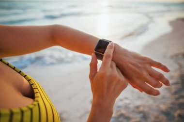 Closeup on young woman in sport style clothes on the beach at sunset using smart watch using app to track fitness activity.