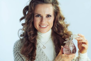 smiling female applying perfume on winter light blue background