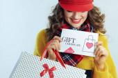 smiling modern woman shopper showing gift certificate