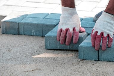 gloved hands lay paving slabs on the sand. bright sunlight