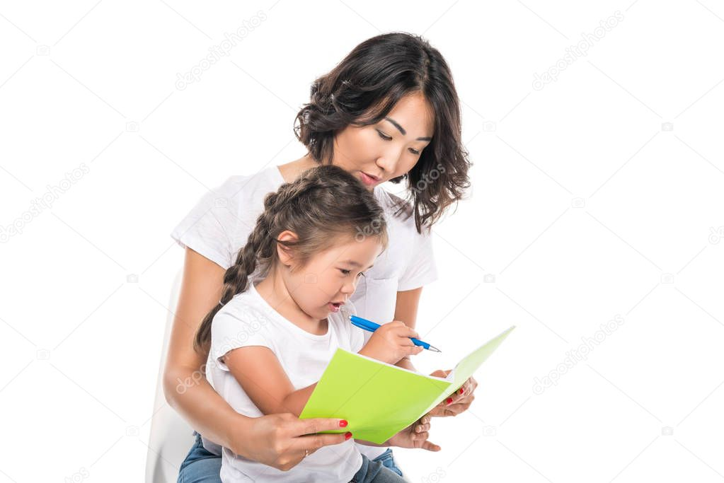 mother and daughter writing in copybook