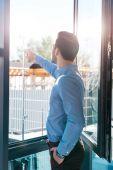 Fotografia uomo daffari che indica alla finestra