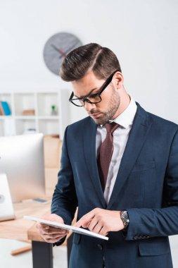 Handsome young businessman in eyeglasses using digital tablet stock vector