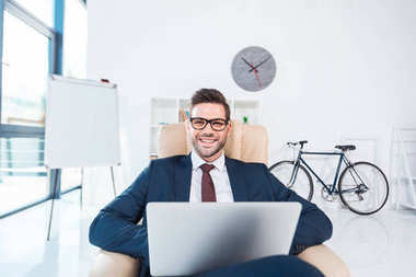 Handsome young businessman in eyeglasses using laptop and smiling at camera in office stock vector
