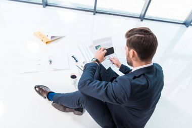 businessman with smartphone and papers