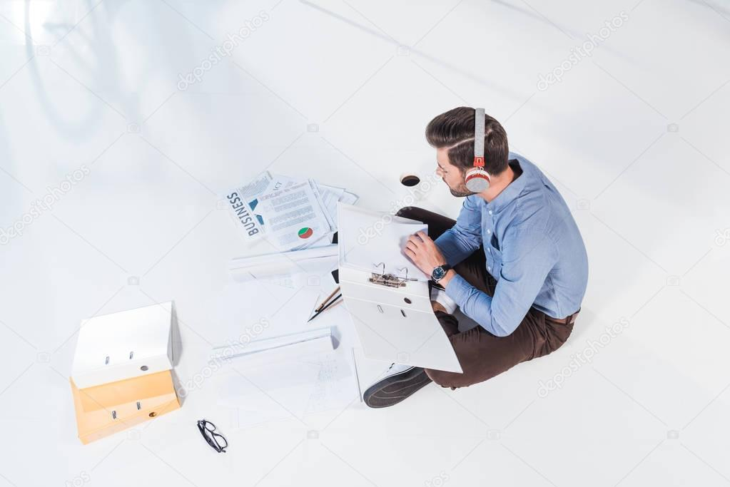 businessman in headphones working with papers