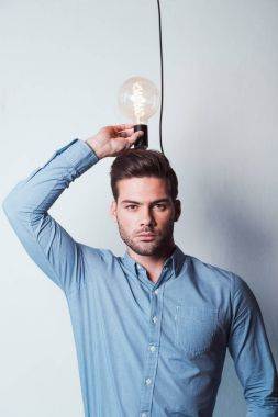 Young businessman holding light bulb and looking at camera on grey stock vector