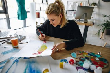 Concentrated female fashion designer drawing watercolor sketch at workplace stock vector