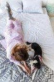 pohled ženy v pyžamu ležel na posteli s roztomilé štěně