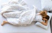 fiatal nő alszik az ágyban reggel felülnézete