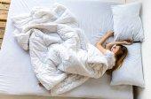 pohled mladé ženy spí v posteli ráno