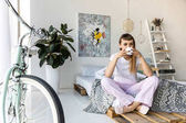 Fotografia giovane donna che beve il caffè mentre si riposa sul letto mattina a casa