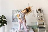 Veselá mladá žena v pyžamu tančí v ráno doma na posteli