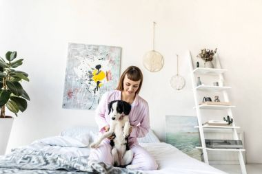 portrait of pretty woman in pajamas holding little puppy while resting in bed at home