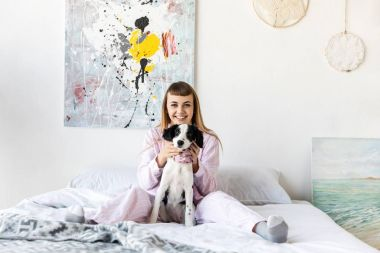 happy woman in pajamas and cute little puppy resting on bed in morning at home