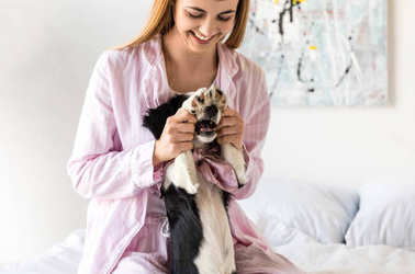 happy woman in pajamas and cute little puppy having fun in morning at home