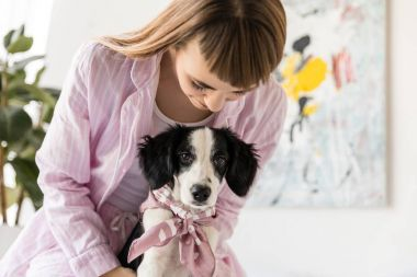 portrait of woman in pajamas and cute little puppy in morning at home