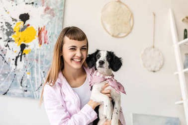 portrait of happy woman holding adorable puppy in hands at home