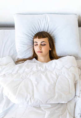 overhead view of young woman sleeping in bed in morning