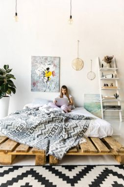 focused young woman using laptop while resting in bed in morning at home
