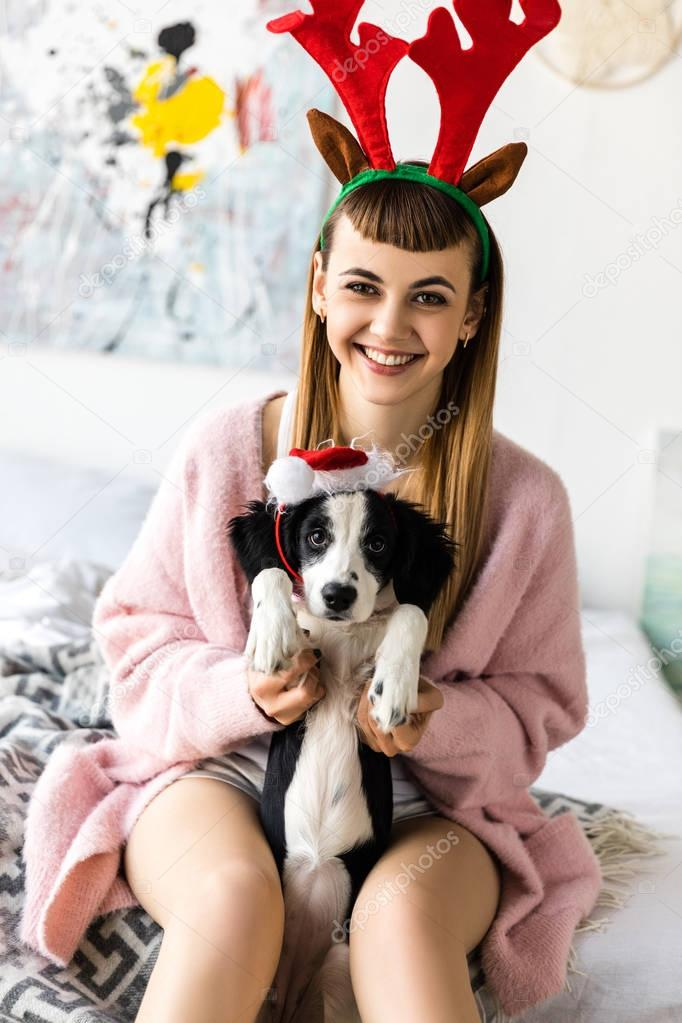 portrait of smiling woman with deer horns on head and puppy in santa hat