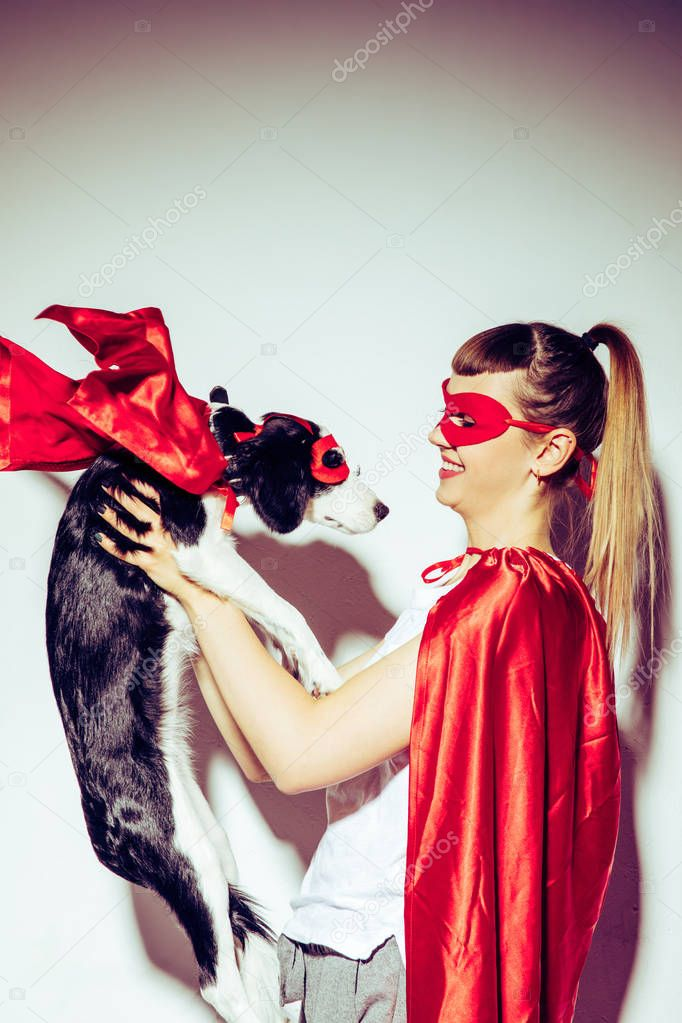 side view of cheerful woman looking at little puppy in superhero costume in hands