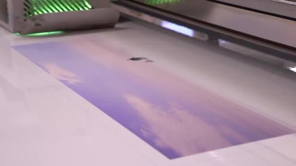 UV tiskárna. Tisk na filmu. Zařízení funguje. Zblízka / tiskárna tiskne na filmu. Tisk držák posunul o pracovní oblasti.
