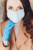 Ijedt fiatal nő orvosi maszkban áll a szürke háttér felett.