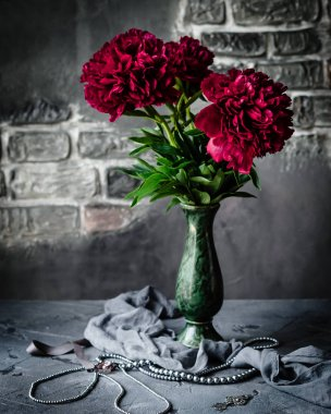 Red peonies in green vase with necklace